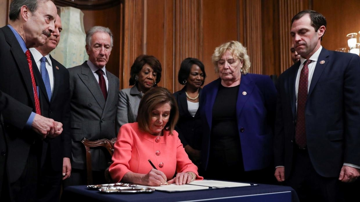 House Speaker Nancy Pelosi signs the articles of impeachment using  a set of commemorative pens with her signature inscribed onto them.