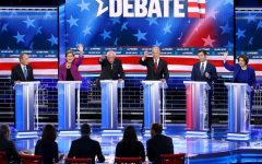 Six Democratic candidates vie for the moderators' attention as they participate in the presidential primary debate in Las Vegas
