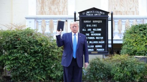 President Donald Trump holding the Holy Bible backwards and upside-down in front of a church he does not go to.